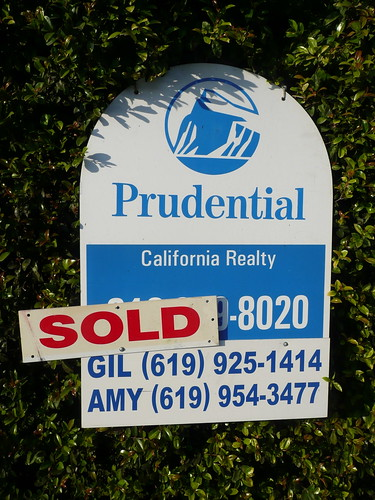 a real estate sign with the sold label attached