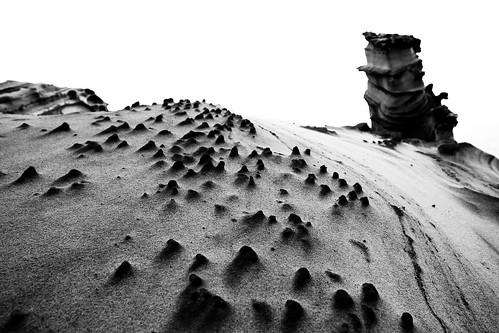 奇岩。黑白處理過的照片,很多人在沙漠中看著霜淇淋