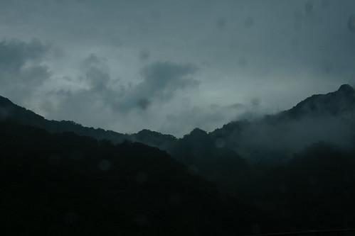 遠方的山巒,映照著車窗上的雨滴,好像髒了,卻又很乾淨。