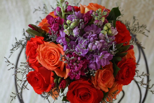 Flowers used were purple stock deep yellow and orange roses