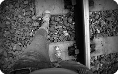one step at a time... (mary ann.) Tags: blackandwhite bw green self myself blackwhite rocks traintracks pebbles adventure stepping converse far chucks hiddenplace onestepatatime girlwearingchucks focalzoom