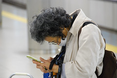 (colinbooks) Tags: old woman station japan japanese technology phone mask culture cell nippon posture oldandnew hunch hunched