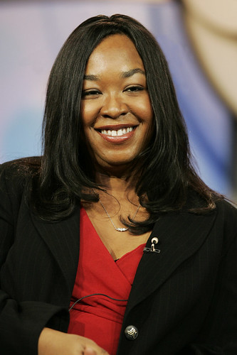 Shonda Rhimes, a Black woman seated at an interview. She is smiling broadly for the camera.