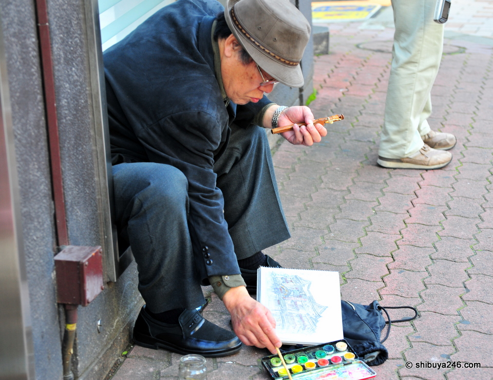 Going about the work of painting without noticing people around him.