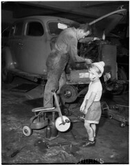 Young boy with dinky in car workshop while his father (?) services a car, Bondi, 6 October 1955 / Ern McQuillan (State Library of New South Wales collection) Tags: cute ford jack oil beanie mechanic dinky   denimshorts   pompomhat