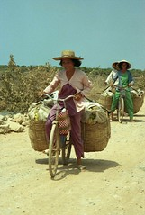 Women on bicycle with big baskets; near Hon Chong, Mekong River Delta, Vietnam (Lon&Queta) Tags: people portraits asia hats vietnam 1995 kiengiang scanneg gpsapproximate timeincorrect