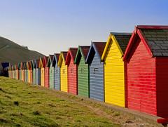 Behind the beach huts (pixiepic's) Tags: sky seaside hills roofs colourful beachhuts embankment slates platinumheartaward