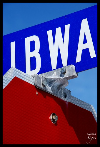 A bright red Stop sign with a bright blue road sign above it, with the letters BWA visible, against a blue sky.