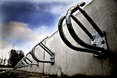 School is out. (nokkie1) Tags: blue lines clouds concrete vanishingpoint dof geometry steel curves bicyclestand