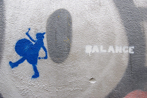 graffiti: to the far right, the word Balance, then a grey circle, the, to the far right, a blue bass drummer, marching away