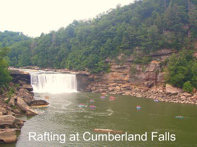 cumberland falls from a distance showing the whole falls falling over the cliff and huge rocks of either side and hills with trees of either side