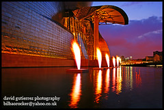 The Bilbao Guggenheim on Fire (david gutierrez [ www.davidgutierrez.co.uk ]) Tags: city travel bridge blue light vacation sky urban cloud holiday color colour reflection building art tourism water museum architecture night clouds composition wonderful river fire photography design photo amazing fantastic europe skies cityscape dusk vibrant modernart sony centre flames great cities gehry center structure architectural bilbao explore nighttime 350 hour stunning excellent nights guggenheim metropolis bluehour alpha fabulous topf100 bizkaia dt basquecountry municipality edifice f4556 1118mm sonyalpha theunforgettablepictures platinumheartaward sonyalpha350 alpha350 newgoldenseal sonyalphadt1118mmf4556 sony350dslra350
