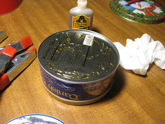 Gluing lids to bottom of tins