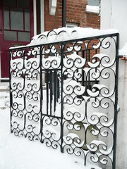 Photograph of snow on a wrought iron gate.