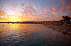 Naama Bay sunset (WomEOS) Tags: sunset holiday mountains beach colors umbrella redsea egypt sharmelsheikh 2009 naamabay