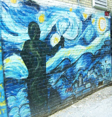 graffiti of stars painted on a brick wall; the painting also shows the silhouette of a person holding a spray can, creating the art.