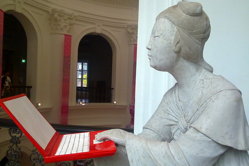 Ancient statue with modern notebook