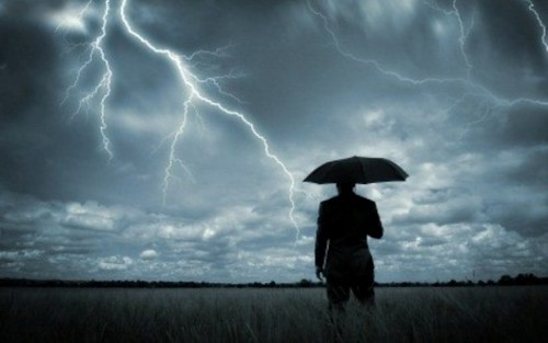 A businessman holding an umbrella in a storm. by jason.wheeler