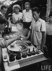 US Ambassador Henry Cabot Lodge Jr. (C) and his wife standing with Fred Flott (L) watching a food vendor serve a customer. par VIETNAM History in Pictures (1962-1963)