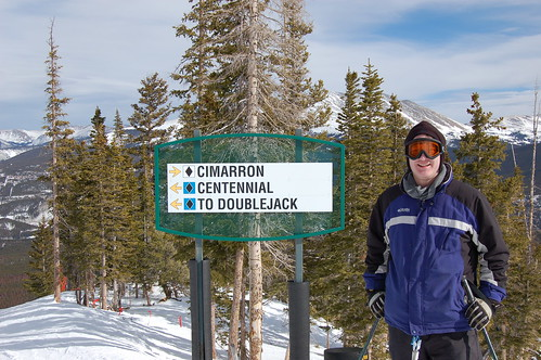 Dan in front of a blue/black ski run sign