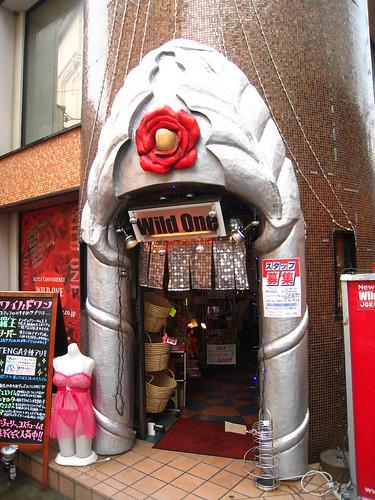 Sex shop con una flor roja en la entrada class=