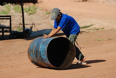 Rolling a barrel down the street (Greg - AdventuresofaGoodMan.com) Tags: southeastasia laos lao pdr