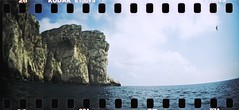Cliff face from a boat (The Hamster Factor) Tags: sea cliff film water race xpro lomography crossprocessed mediterranean sardinia kodak panoramic ektachrome e100vs alghero sprocketrocket