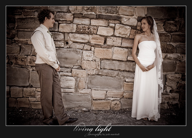 Bride and groom looking at each other in front of a stone wall on King Street, Newcastle.