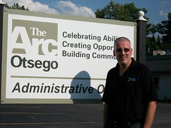 Justin standing on the front of The Arc Otsego's billboard