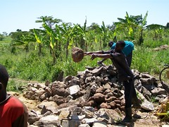 A local man helps to move stones closer to the site