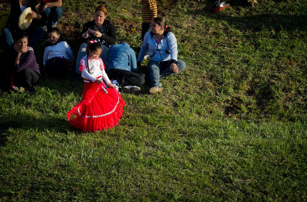 Mientras buques extranjeros saludaban en la Bahía de Asunción, una niña observaba y bailaba, ataviada con un vestido típico. (Tetsu Espósito - Asunción, Paraguay)