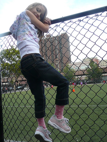 climbing the fence while bain plays soccer.