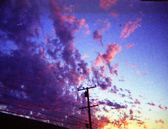 We are the explosion in which lies the dream (QsySue) Tags: pink blue sunset sky clouds purple powerlines orangecounty huntingtonbeach spycam ansco50 110filmcamera titleisadaxriggslyric tinylittleplasticthing smallestcameraever