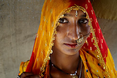 A Traditional Rajasthani Woman ( Poras Chaudhary) Tags: orange woman india colors yellow zeiss 35mm eyes traditional ornaments carl pushkar jewllery rajasthan rajasthani classicportrait nikond3
