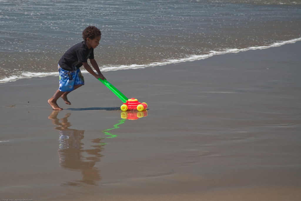 Mowing Water! Youngster with plastic lawn mower toy playing in the wet sand at water's edge on Morro Strand State Beach