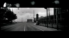 trackscape #1 (mugley) Tags: road city bridge trees urban blackandwhite bw panorama film 35mm toycamera tracks australia melbourne victoria lightleak negative xp2 wires epson cbd 135 ilford urbanlandscape tramstop c41 latrobest v700 blackbars remandcentre haking ilfordxp2super400 ilfordxp2400super port1010 melbourneassessmentprison plasticpanocamera