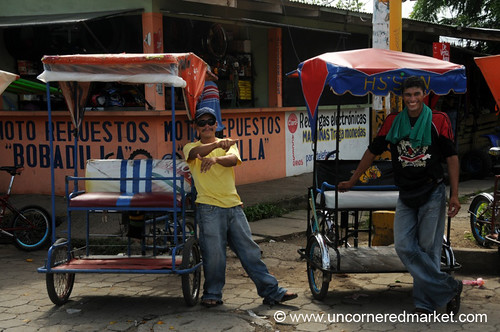A couple of bicycle taxi drivers ham it up for the camera at the bus station in Rivas, Nicaragua - Photo by Uncornered Market