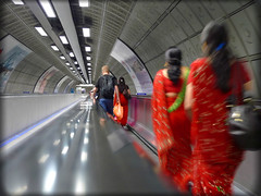Running red (Che-burashka) Tags: red motion travelling london underground walking vanishingpoint moving cosmopolitan women metro indian escalator tube diversity fast running dailycommute waterloo rush commute scifi multicultural sari abus londonist lx3