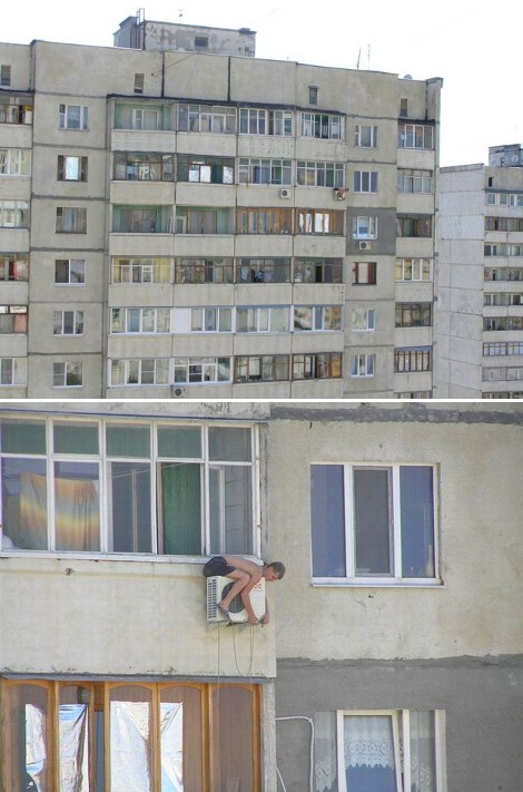 Man sitting on aircon unit on top of very tall building