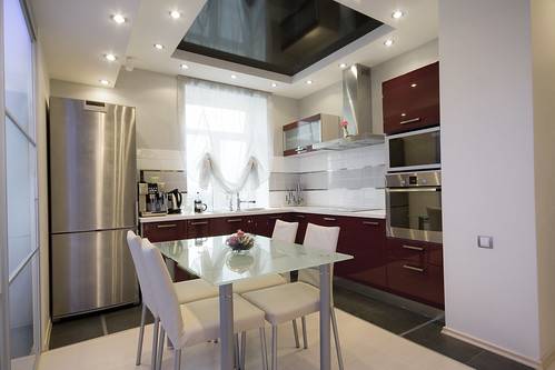 Modern-kitchen-design-with-glass-table-soft-leather-chairs-crimson-drawers-build-in-oven