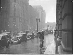 Rain, Martin Place, Sydney, 1937 / by Sam Hood (State Library of New South Wales collection) Tags: woman chevrolet rain umbrella buildings streetlamps sydney automobiles martinplace streetscapes raincoats statelibraryofnewsouthwales samhood