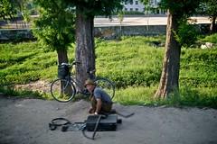 A man fixes a bike by the side of the road (Joony_Boy) Tags: poverty north korea communism kimjongil northkorea dprk kimilsung