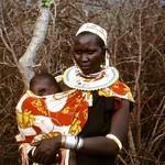 Tansania - Massai-Mama mit Baby - vor Dorfumzäunung, 478