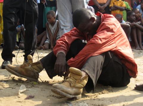 Un voleur menotté et assis à même le sol