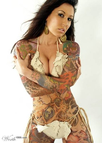 Bikini woman with tattoo abstractedly at body