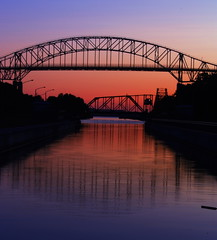 International Bridge (Billy Wilson Photography) Tags: city bridge sunset ontario canada color colour reflection water silhouette architecture digital canon reflections eos rebel canal large silhouettes sunsets international xs soo northern span saultstemarie northernontario algoma internationalbridge billywilson bridgespan