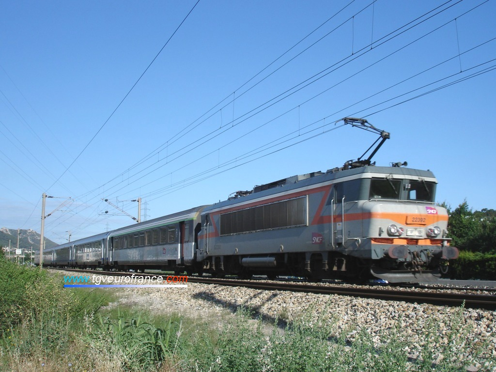 A dual-voltage BB 22200 electric SNCF locomotive hauling a passenger train on the Marseille - Nice railway