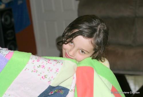 Rylee cuddles her new quilt