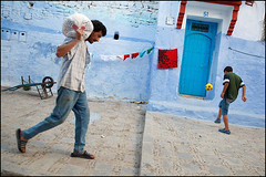 blue door - Chefchaouen (Maciej Dakowicz) Tags: africa street city boy people game work ball children football play morocco maroc maghreb medina chaouen load chefchaouen carry