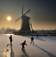 global-warming off-day :) (HanslH) Tags: windmill ice skating kinderdijk lowsun longshadows winter netherlands bravo nikond3 sun mill contralight mood nederland silhouettes reet goldenbrown oerhollands dutch typicallydutch leuropepittoresque